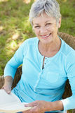 Senior woman reading a book. Smiling Royalty Free Stock Photography