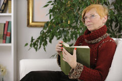 Senior woman reading a book. In the living room Royalty Free Stock Photos