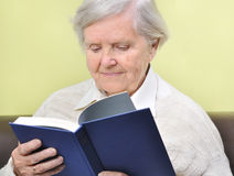 Senior woman reading book. Senior woman reading book in home Royalty Free Stock Photo