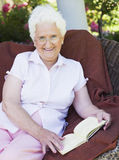 Senior woman reading book. Sitting on garden chair Stock Images