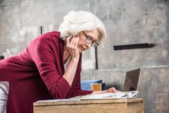 Attractive senior woman in eyeglasses reading book while sitting at desk with laptop royalty free stock image
