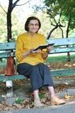 Senior woman reading book autdoors Stock Image