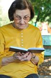 Senior woman reading book autdoors Stock Photos