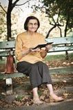 Senior woman reading book autdoors Royalty Free Stock Photography