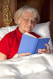 Senior woman reading a book in bed Royalty Free Stock Photos