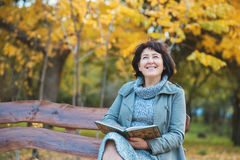 Senior woman is reading the book and dreaming in the park Stock Photos
