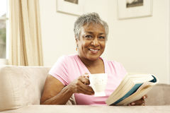 Senior Woman Reading Book With Drink Stock Photos