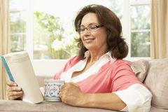 Senior Woman Reading Book With Drink At Home Royalty Free Stock Image