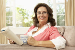 Senior Woman Reading Book With Drink At Home Royalty Free Stock Photos