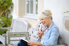 Senior woman reading book enjoying Royalty Free Stock Image
