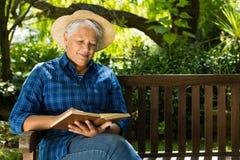 Senior woman reading book. In the garden Stock Photo