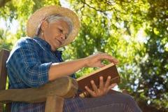 Senior woman reading book. In the garden Royalty Free Stock Photos