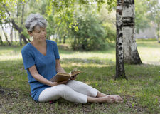 Senior woman reading a book. In the garden. Gray-haired woman sitting on the green grass Royalty Free Stock Photos