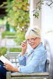 Senior woman reading book in the garden Royalty Free Stock Image