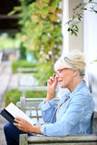 Senior woman reading book in the garden stock photography