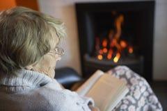 Senior Woman Reading Book At Home. Senior Woman Reading Book By Fire At Home Royalty Free Stock Image
