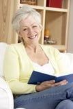 Senior Woman Reading Book At Home. Smiling Royalty Free Stock Photo