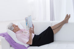 Senior woman reading a book at home Stock Photography