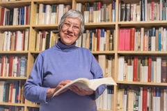 Senior woman reading a book at home. Happy expression. A blurred Royalty Free Stock Photography