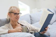 Senior woman reading book at home Stock Photos