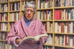 Senior woman reading a book at home. Serious expression. A blurr Stock Photography
