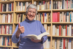 Senior woman reading a book at home. Thumbs up, motivated expres Stock Photo