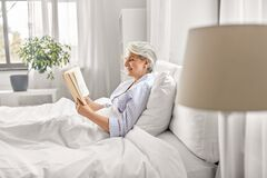 Free Senior Woman Reading Book In Bed At Home Bedroom Royalty Free Stock Photo - 220986785