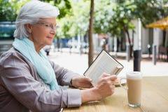 Senior woman reading a book. In outdoor caf Royalty Free Stock Photos