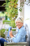 Senior woman reading book outdoors Stock Photography