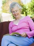 Senior woman reading book outside Stock Photo