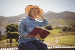 Senior woman reading a book on park bench Stock Photo