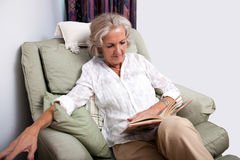 Senior woman reading book while relaxing on armchair at home. Senior women reading book while relaxing on armchair at home Royalty Free Stock Photos