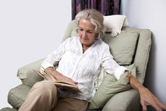 Senior woman reading book while relaxing on armchair at home Stock Photo