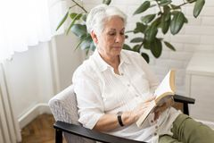 Senior woman reading book. In the room at home Royalty Free Stock Images