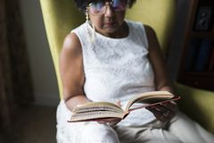 Senior woman reading book in the room Royalty Free Stock Image