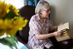 Senior woman reading book while sitting in nursing home Royalty Free Stock Image