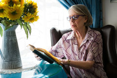 Senior woman reading book while sitting in retirement home Stock Photos
