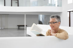Senior Woman Reading Book On Sofa Royalty Free Stock Photography