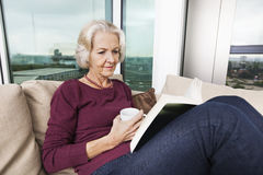 Senior woman reading book on sofa at home Stock Photography