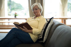 Senior woman reading book on sofa in living room. At home Royalty Free Stock Images
