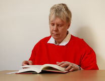 Senior Woman Reading Book at Table Stock Photo