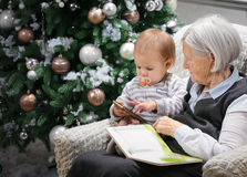 Senior woman reading a book to her baby grandson beside a Christmas tree Stock Images