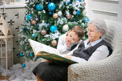 Senior woman reading a book to her grandson. Senior women reading a book to her grandson beside a Christmas tree Royalty Free Stock Photo