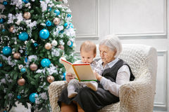 Senior woman reading a book to her great grandson. Senior women reading a book to her great grandson beside a Christmas tree Stock Photo
