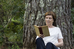 Senior Woman Reading a Book Under the Tree Royalty Free Stock Image