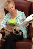 Senior woman reading with cat. A senior woman relaxing and reading with her persian cat on her lap Royalty Free Stock Photography