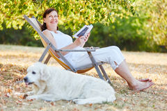 Senior woman reading on a deck chair with dog. In the park Royalty Free Stock Image