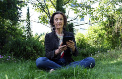 Senior woman reading an e-book in the garden. Senior woman sitting on the ground in the garden reading an e-book with an e-reader Stock Photography