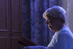 A senior woman reading her book before sleeping Royalty Free Stock Images