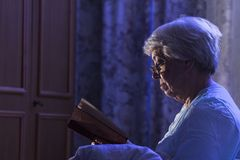 A senior woman reading her book before sleeping Royalty Free Stock Photo